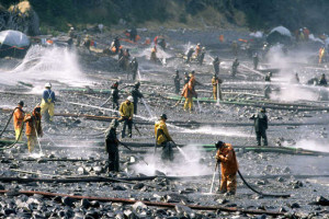 Exxon Valdez oil spill workers use pressure washers to wash oil from the beach on Smith Island, Prince William Sound. The oil was impounded in the water off of the beach and skimmed from the water. Photo by Bob Hallinen, Anchorage Daily News